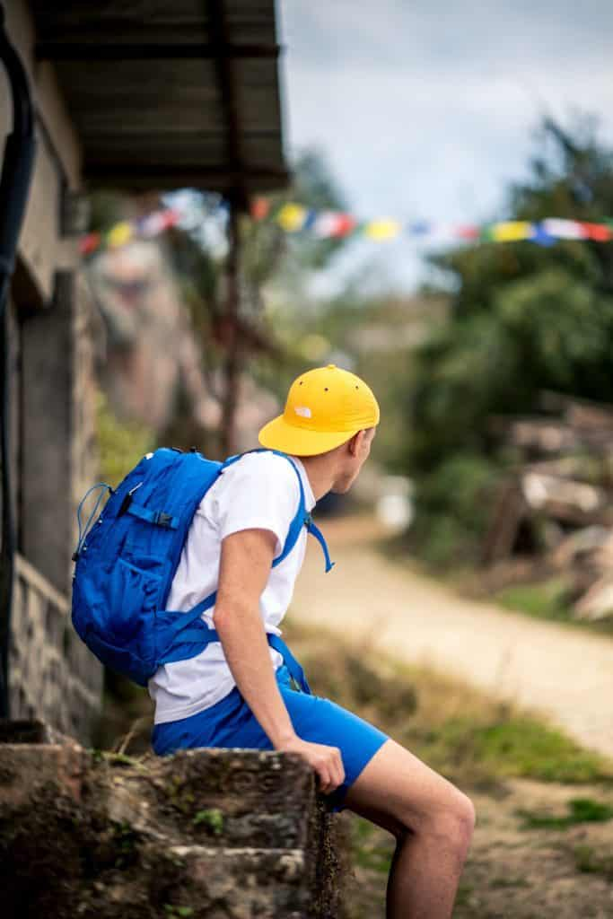 A man sits on a wall wearing a yellow cap and blue rucksack from the north Face Summer collection