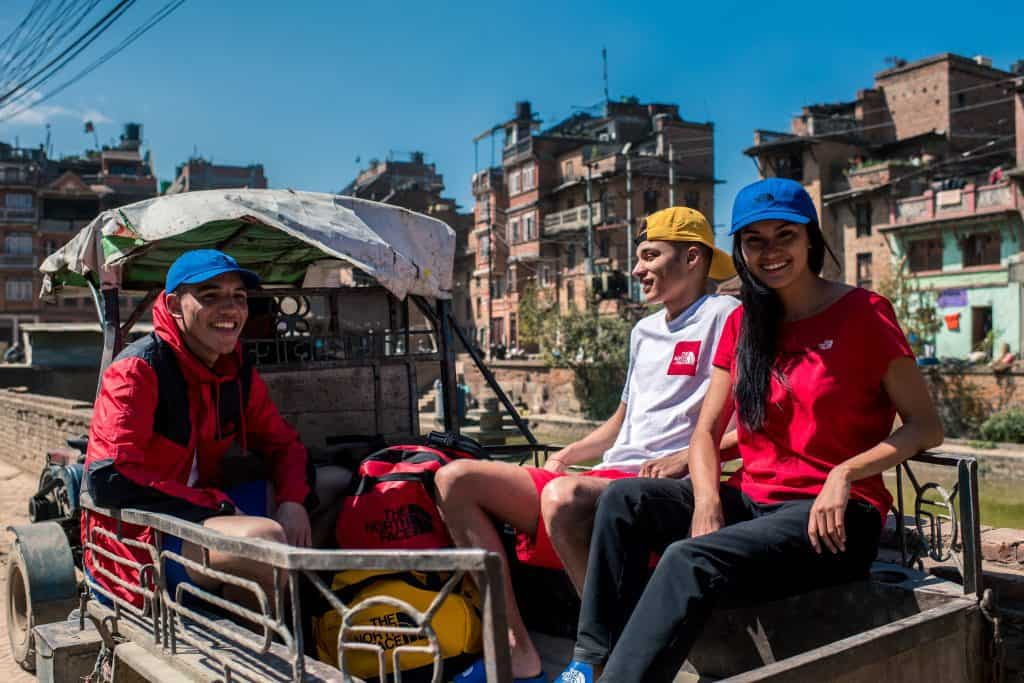 Three people in a truck wearing the North Face Summer collection