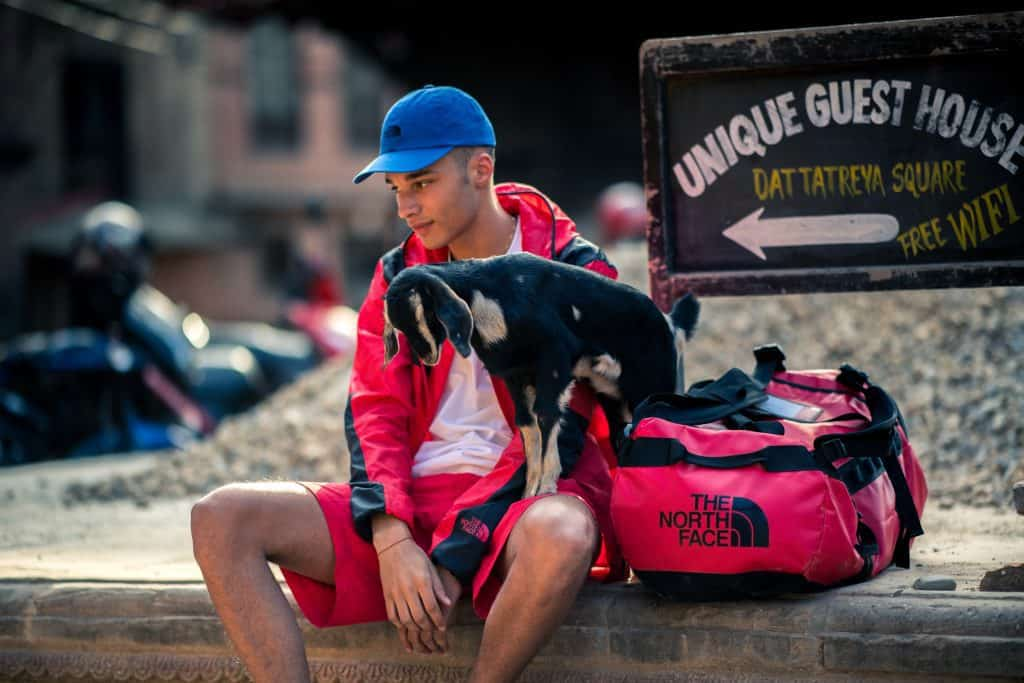 A man sits on a wall with a goat wearing The North Face summer collection