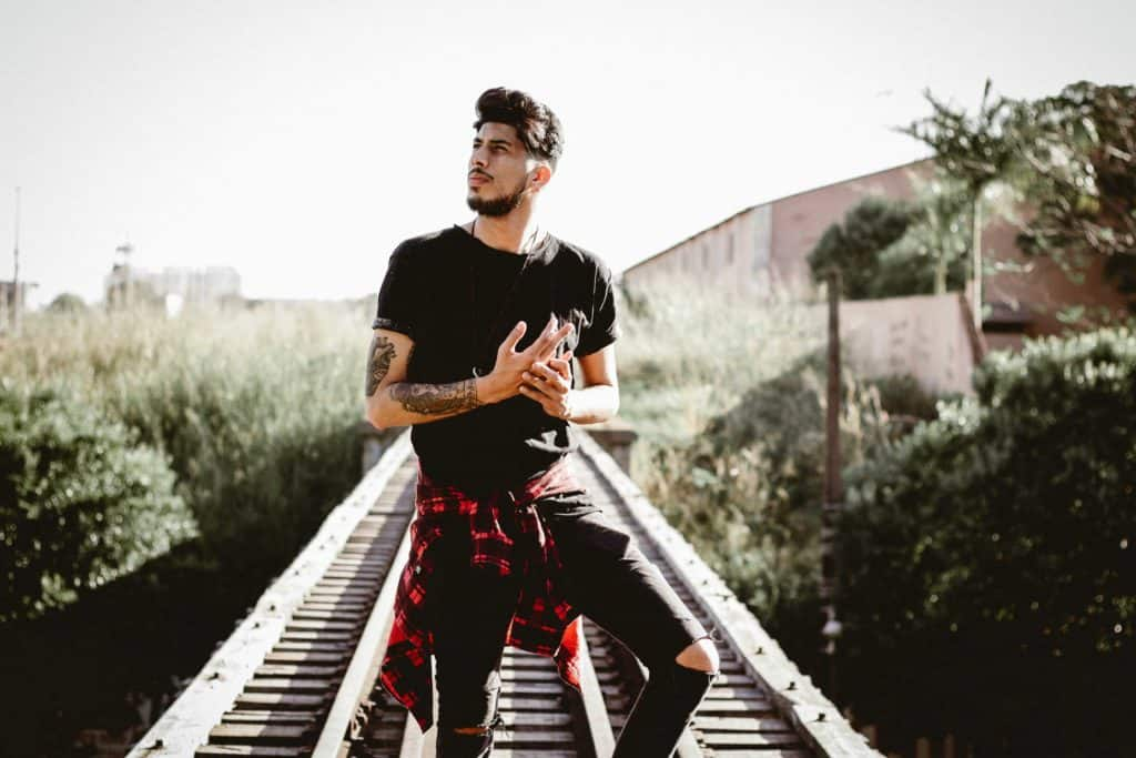A man in black ripped jeans and a black t-shirt stands on a train track