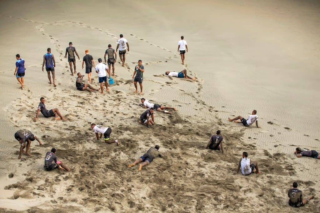 Members of the Fiji 7s squad laying on the sanddunes