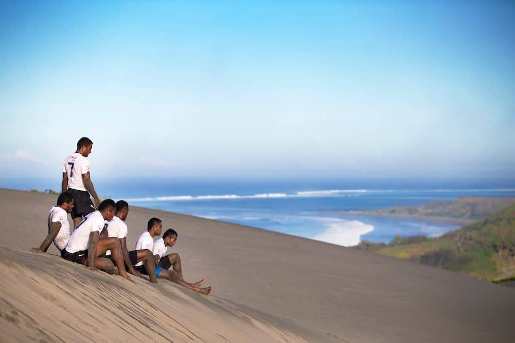 Ben Ryan's Fiji 7s squad sit on the side of a sanddune