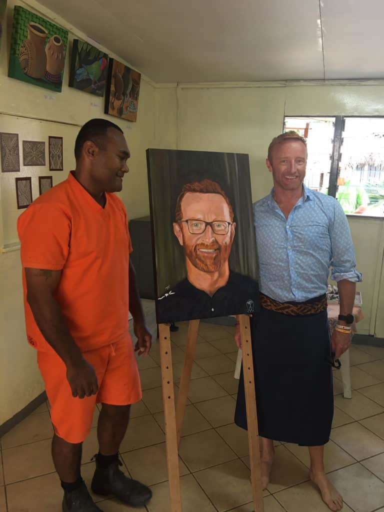 Rugby coach Ben Ryan stands next to a portrait of himself.
