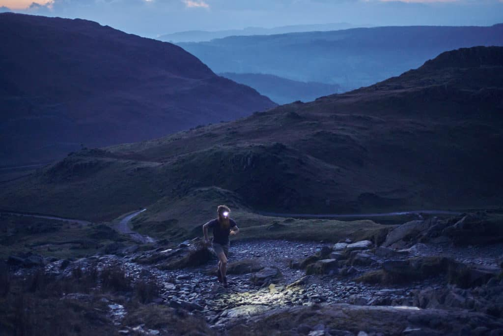 Adventurer Sean Conway running at night through the hills