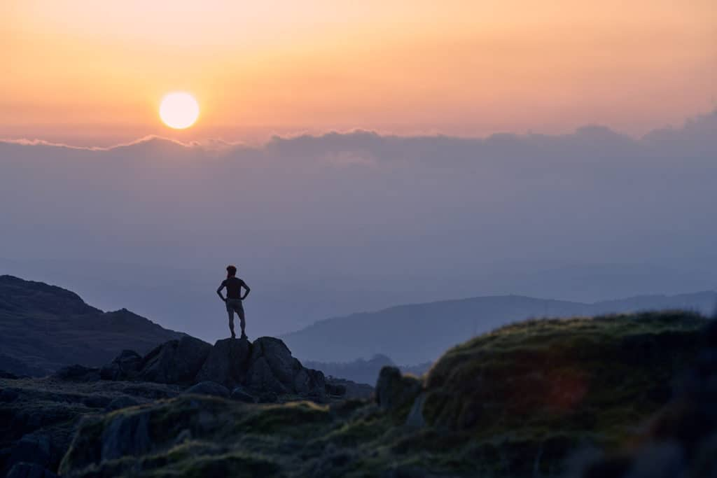 Sean Conway stands in the hilltops at sunset