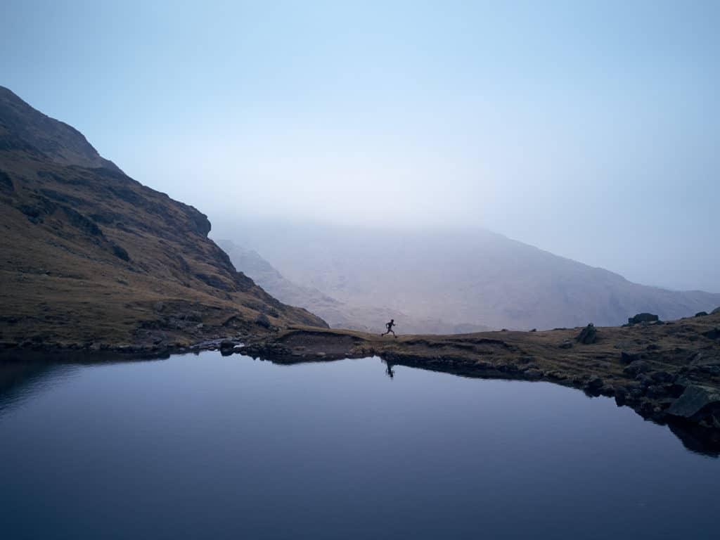 Adventurer Sean Conway runs around a lake in the mountains