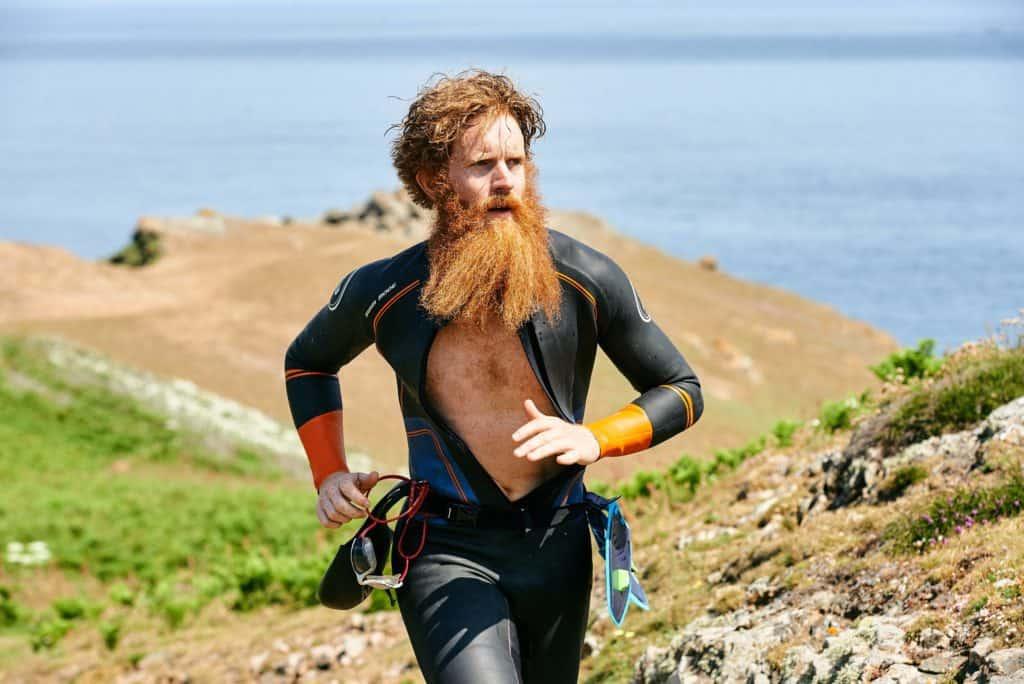 Adventurer Sean Conway running in a wetsuit
