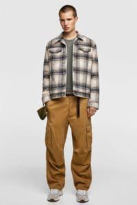 Model wearing check shirt and baggy combat pants