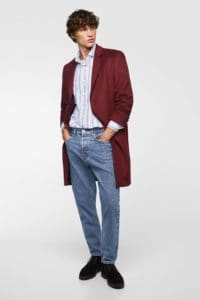 Model wearing blue jeans and an oversized maroon overcoat