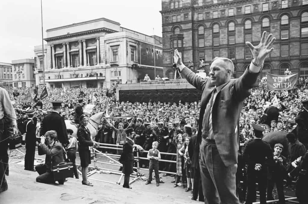 Bill Shankly hands aloft overlooked by a huge crowd inLiverpool city centre