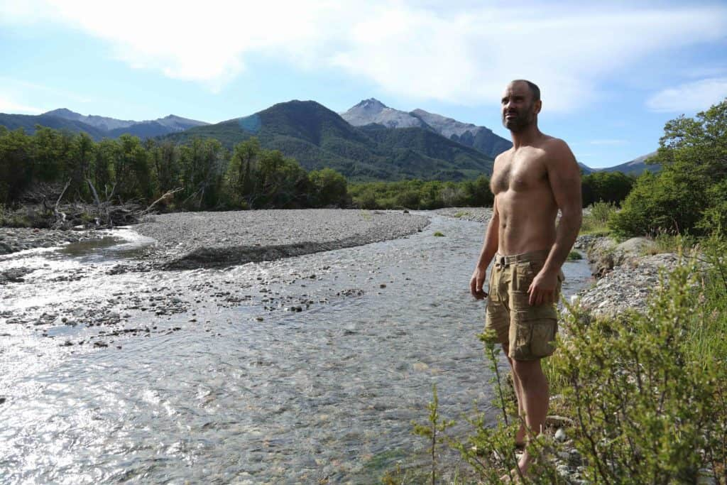 Ed Stafford standing on a river bank in Patagonia.