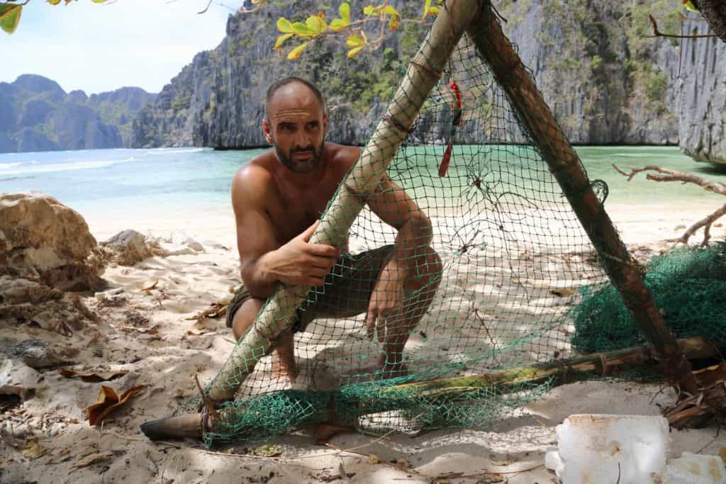 Ed Stafford tying a fishing net to a bamboo frame with the sea and cliffs behind him.