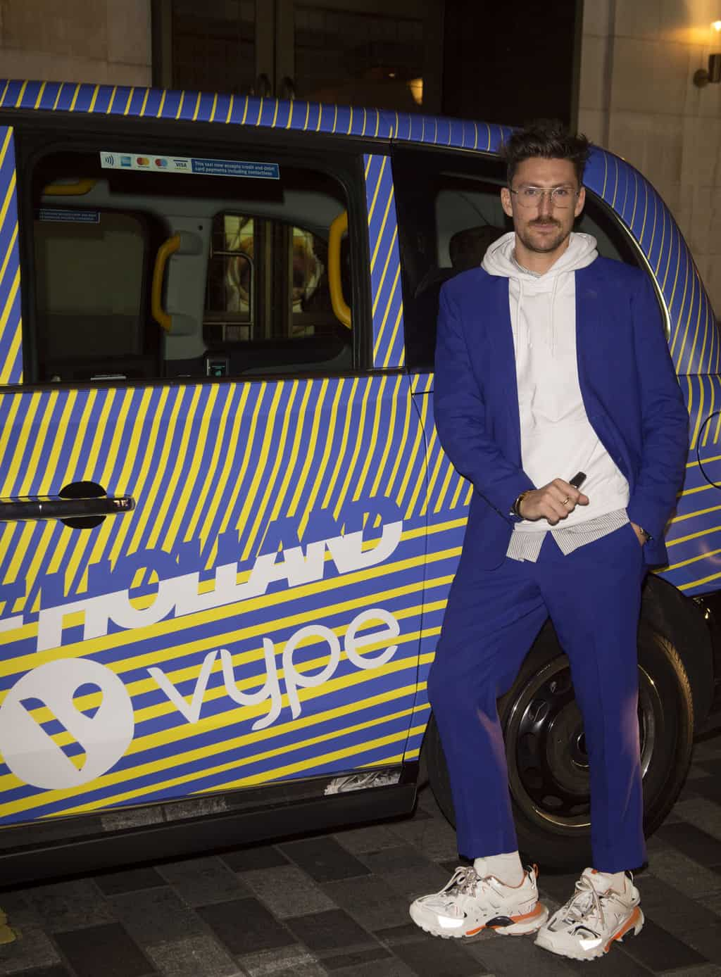 Fashion designer Henry Holland poses next to a London taxi