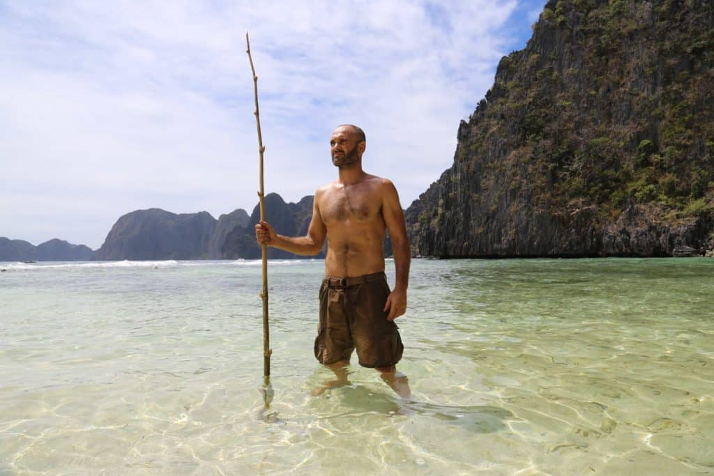 Ed Stafford standing, holding a bamboo rod with the sea and cliffs behind him.