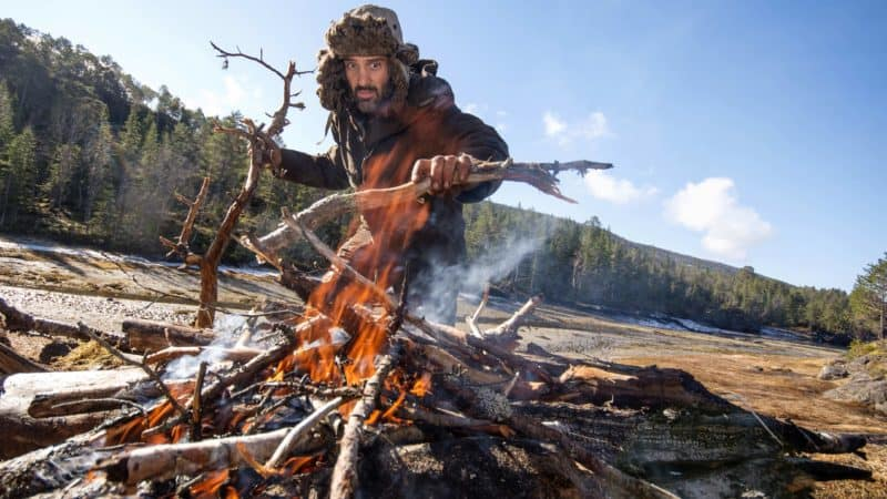 Ed Stafford adding firewood to his fire.