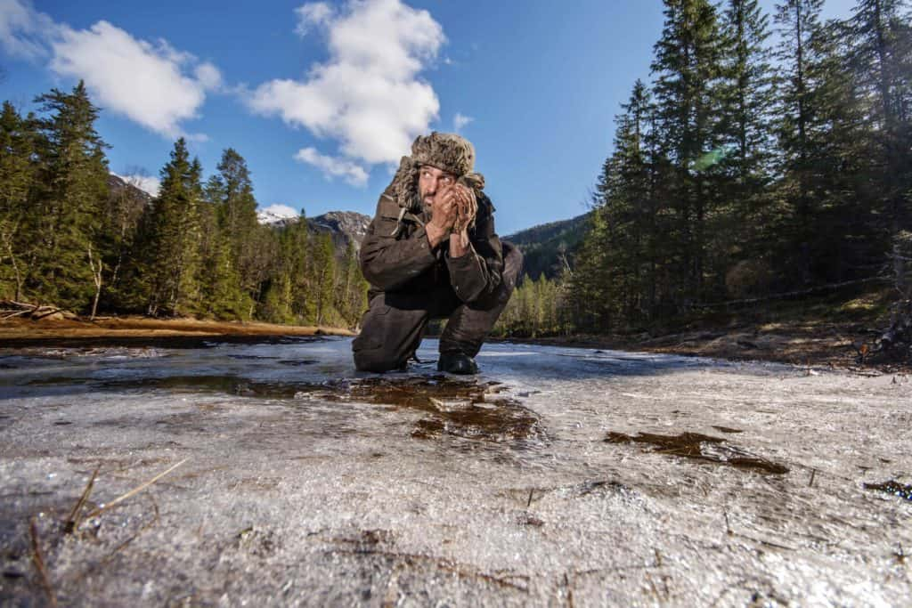 Ed Stafford breaking the ice to collect water.