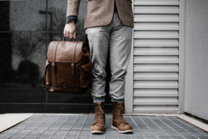 A model in brown leather worker boots holding a brown leather rucksack