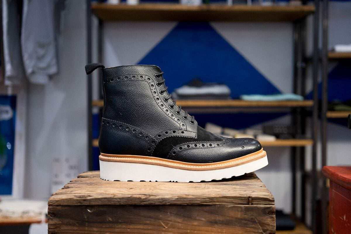 A black leather brogue boot on a wooden stand
