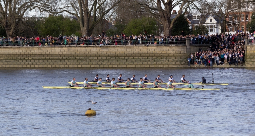 Two teams compete in the boat race on the river thames overlooked by a crowd of people