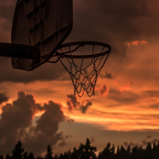 A basketball hoop with dusk sky behind