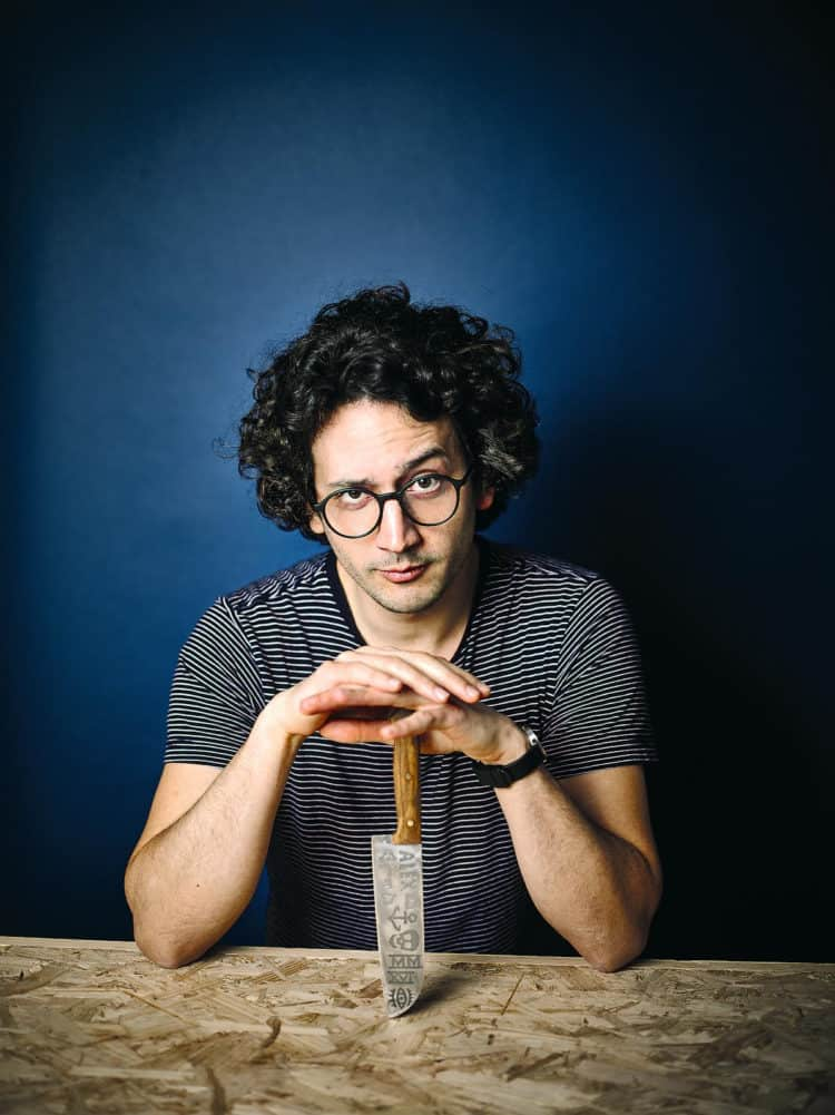 Alexis Ainouz sitting at a table with a chef's knife