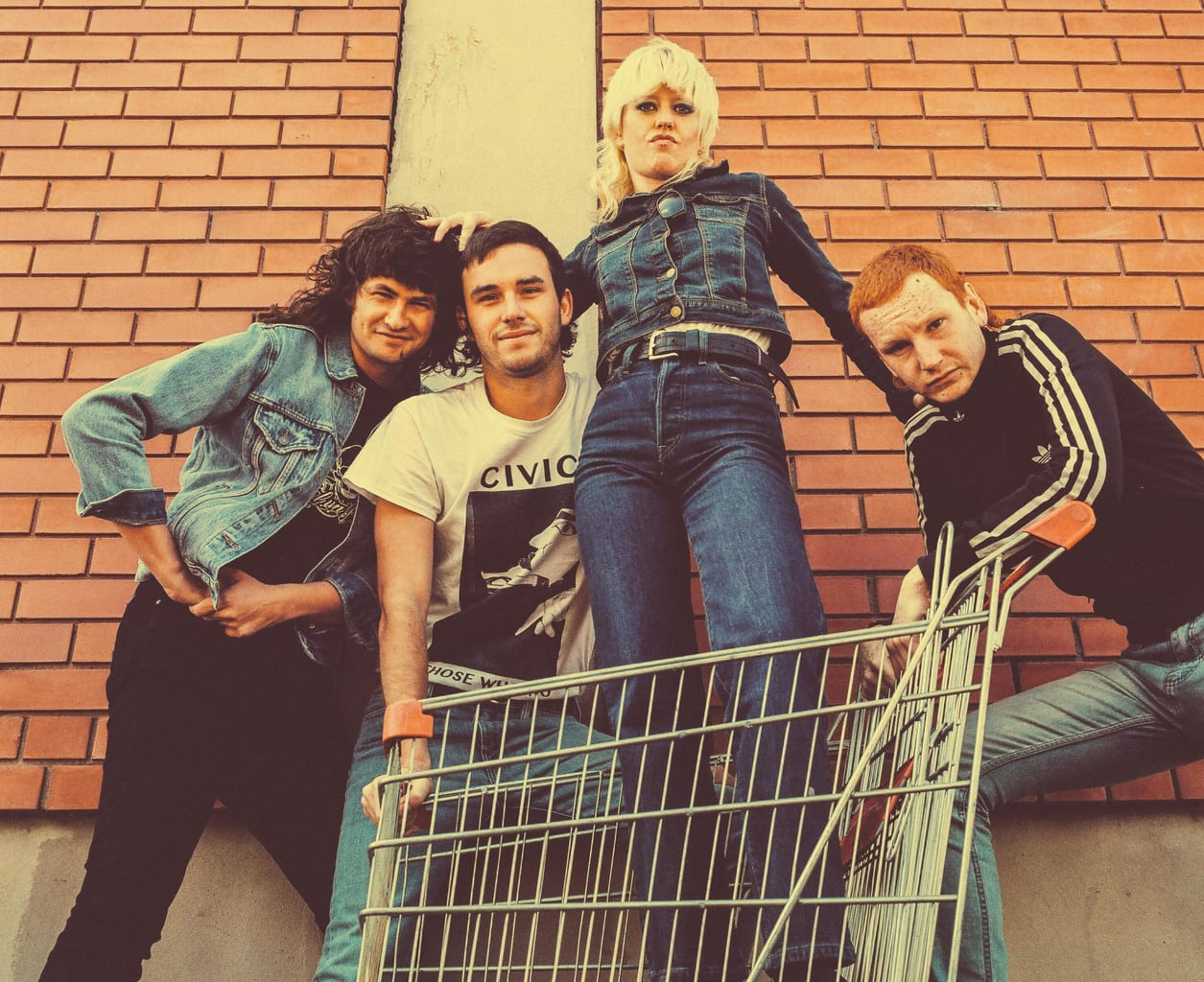 Band Amyl and the Sniffers posing for a photo with lead singer Amy in a shopping trolley