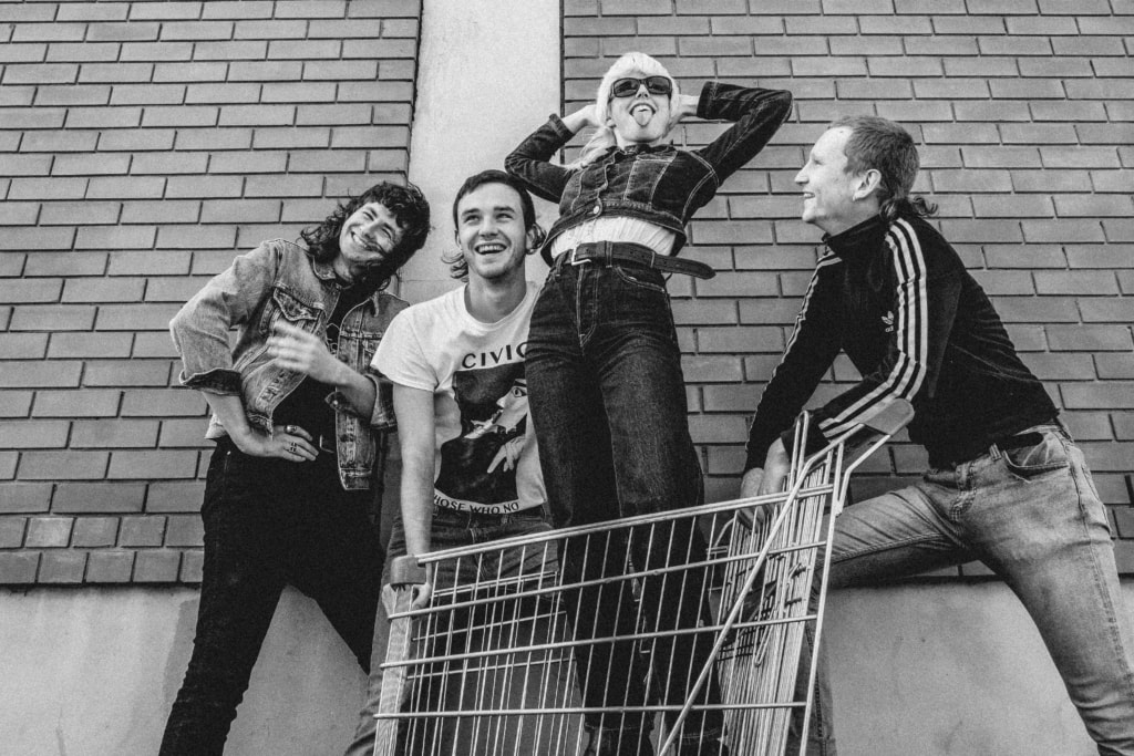 B&W picture of Band Amyl and the Sniffers posing for a photo with lead singer Amy in a shopping trolley