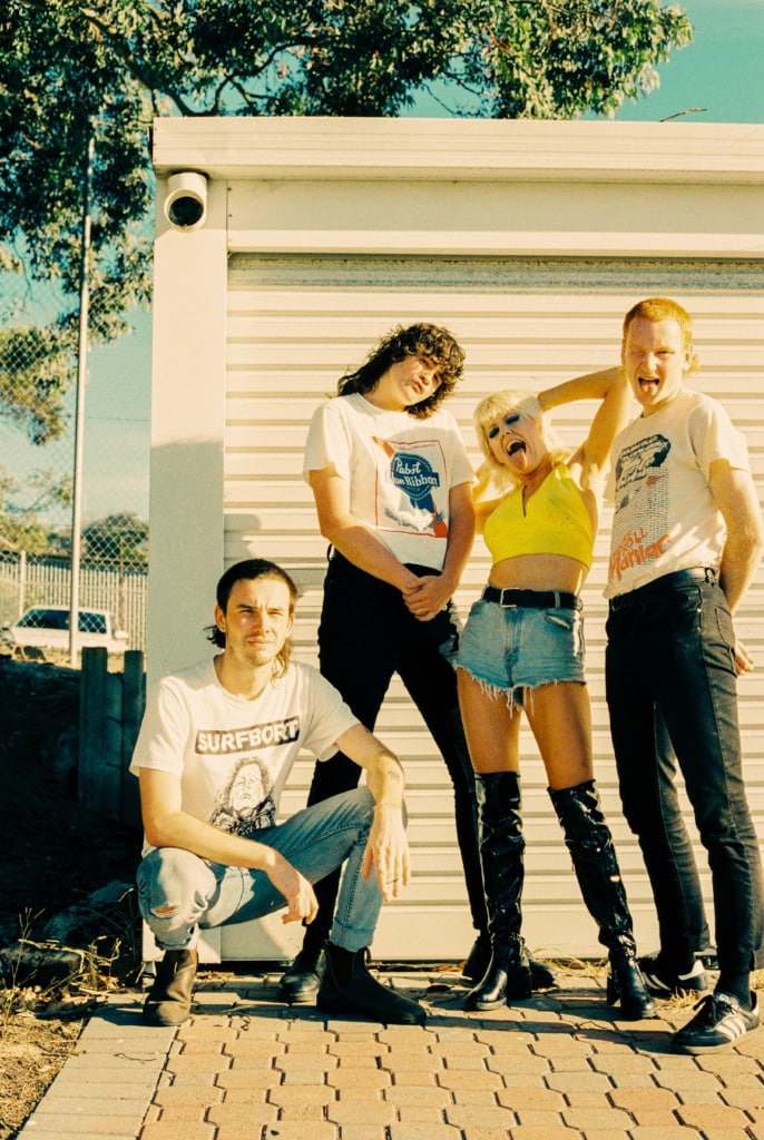 Amyl and the Sniffers pose outside a garage