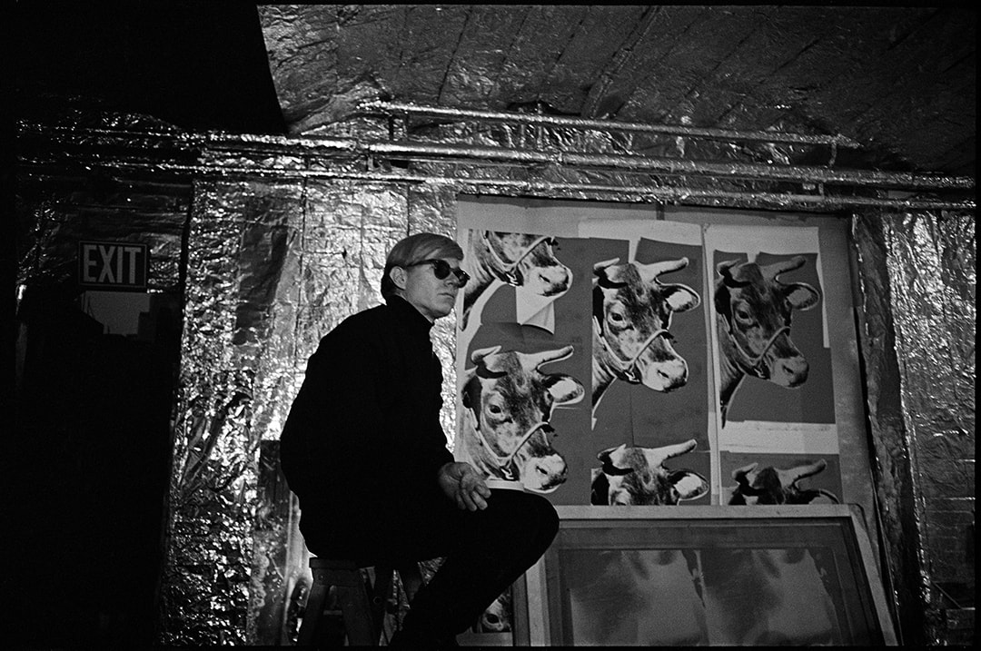 Andy Warhol with Cow Wallpaper at the factory from In and Out of Warhol's Orbit: Photographs by Nat Finkelstein