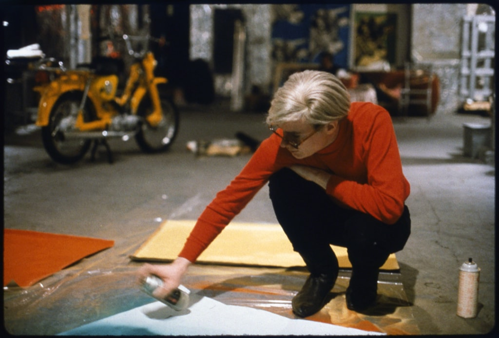 Andy Warhol with spray pain and moped, from In and Out of Warhol's Orbit: Photographs by Nat Finkelstein