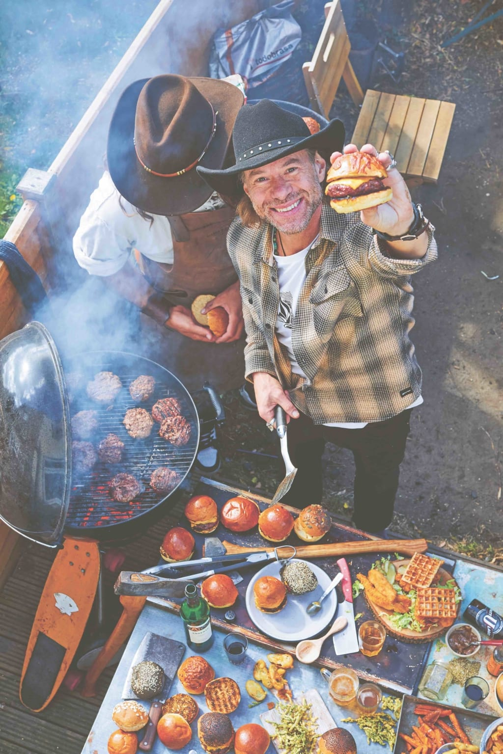 Christian Stevenson aka DJ BBQ holds up a burger to camera while BBQing