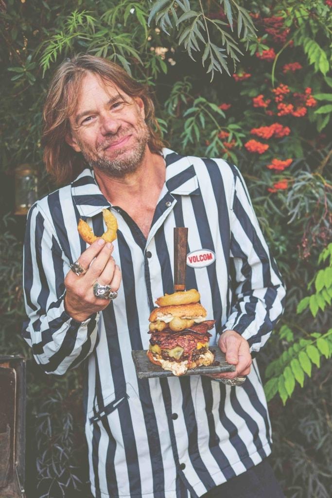 Christian Stevenson aka DJ BBQ holding a burger dressed in a striped shirt