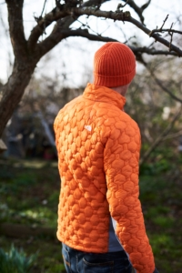 A man wearing a Men's Impendor Thermoball Jacket and orange Finisterre beanie