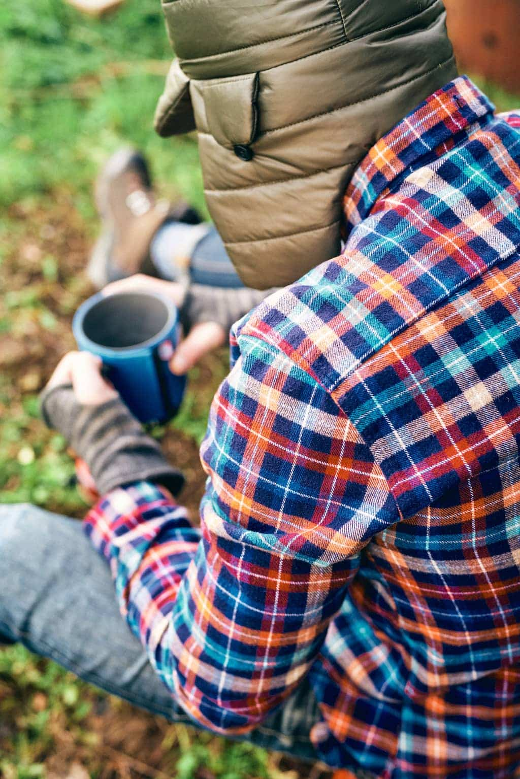 A man sits in the woods drinking coffee