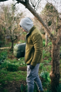 A man carrying a sleeping bag in the woods