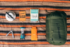 A selection of outdoor essentials laid out on a patterned blanket