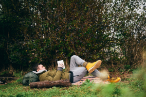 A man lies on a blanket in the woods reading a book