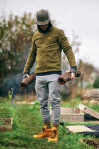 A man carrying two logs in the great outdoors
