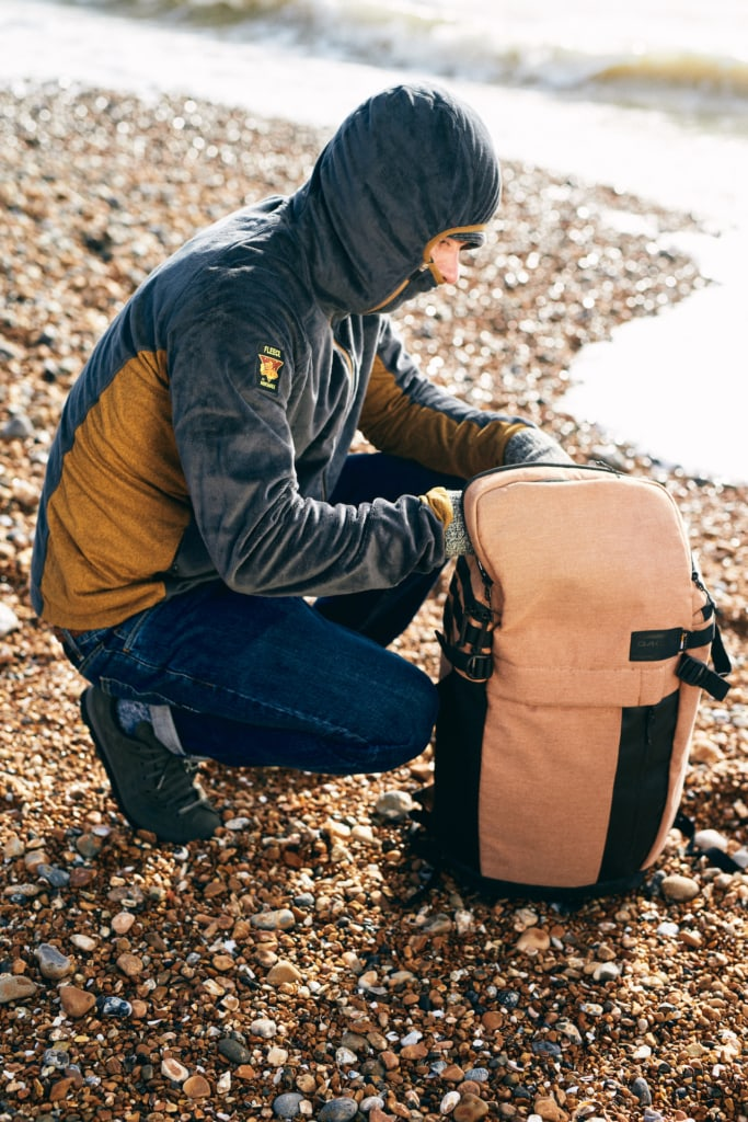 A man kneels down and looks in his backpack on the beach