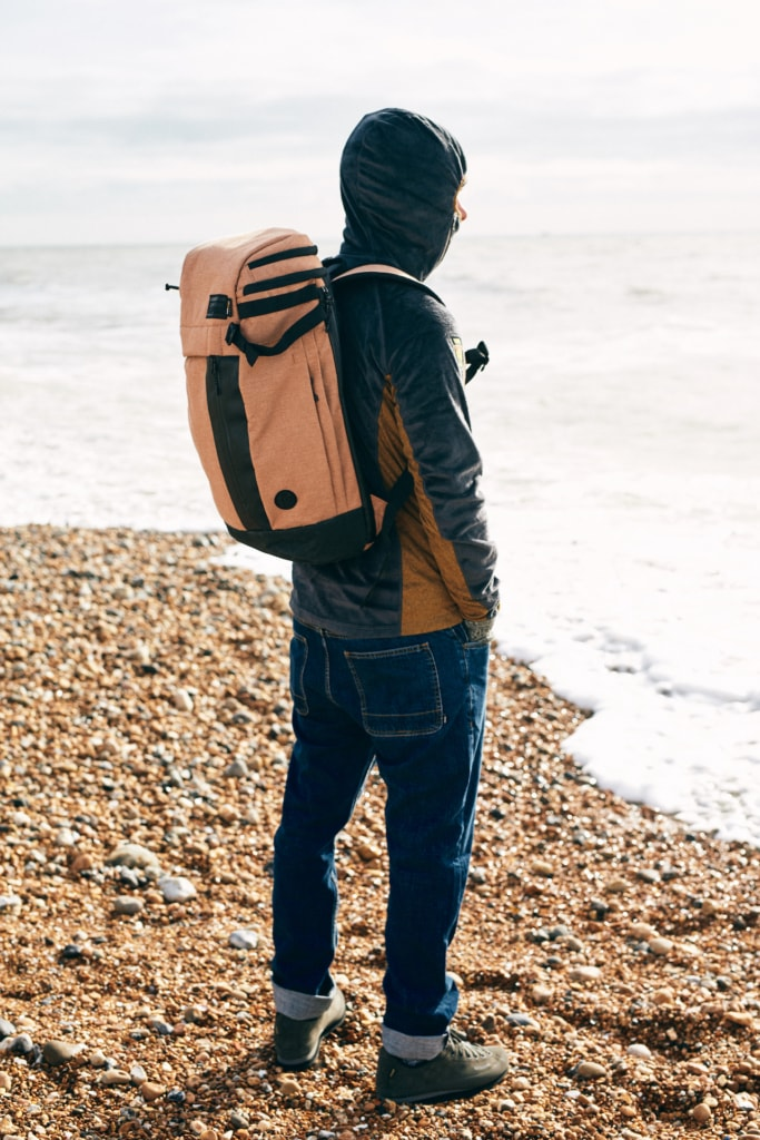 A man wearing a backpack looks out to sea