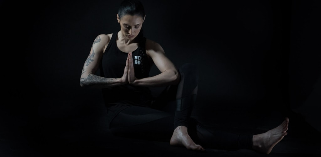 One of Dan Robert's NUK SOO™ proponents sits on the floor in a yoga pose with hands in prayer