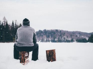 A man sat on a log in the snow