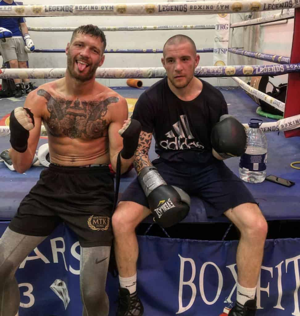 Boxer Mitchell Frearson sits on a ring apron fists raised in fighting pose with sparring partner sat next to him