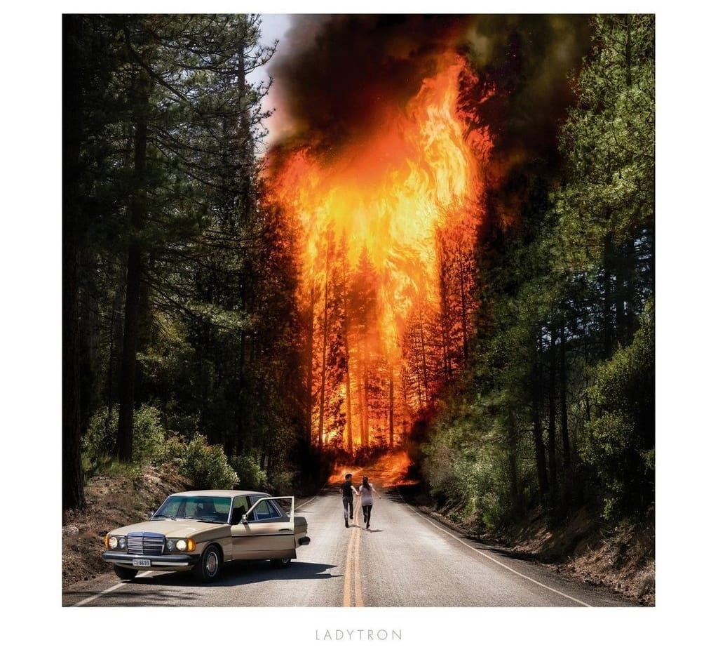 A man and woman abandon a car and run towards a forest engulfed in flames