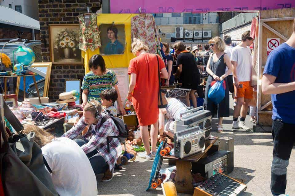 A crowd of people rummage through secondhand goods
