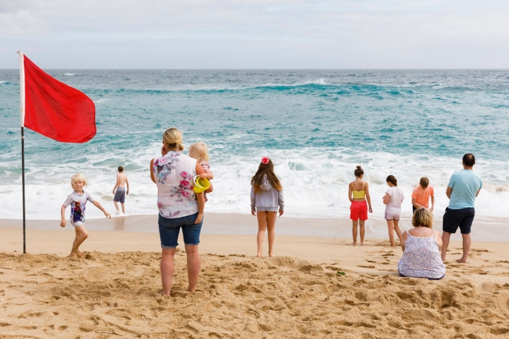 Holidaymakers standing on a beach looking out to sea, with a red flag planted in the sand