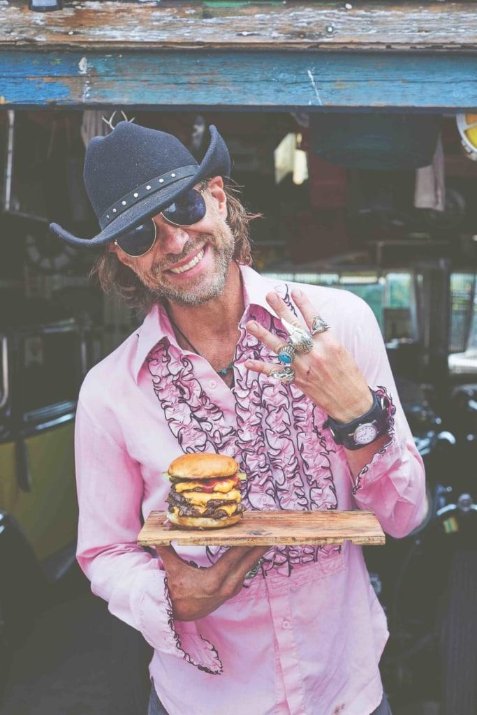 DJ BBQ holding a quad burger