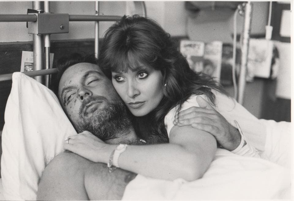 Rocky Taylor in his hospital bed being looked after by his then partner, Marlene.