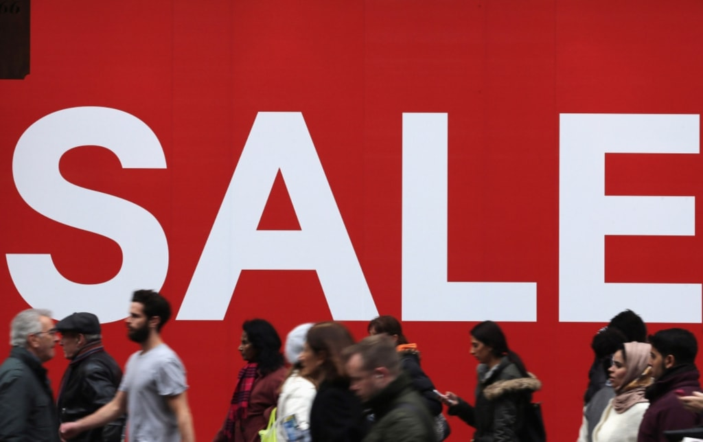 Shoppers walking past a large Sale sign
