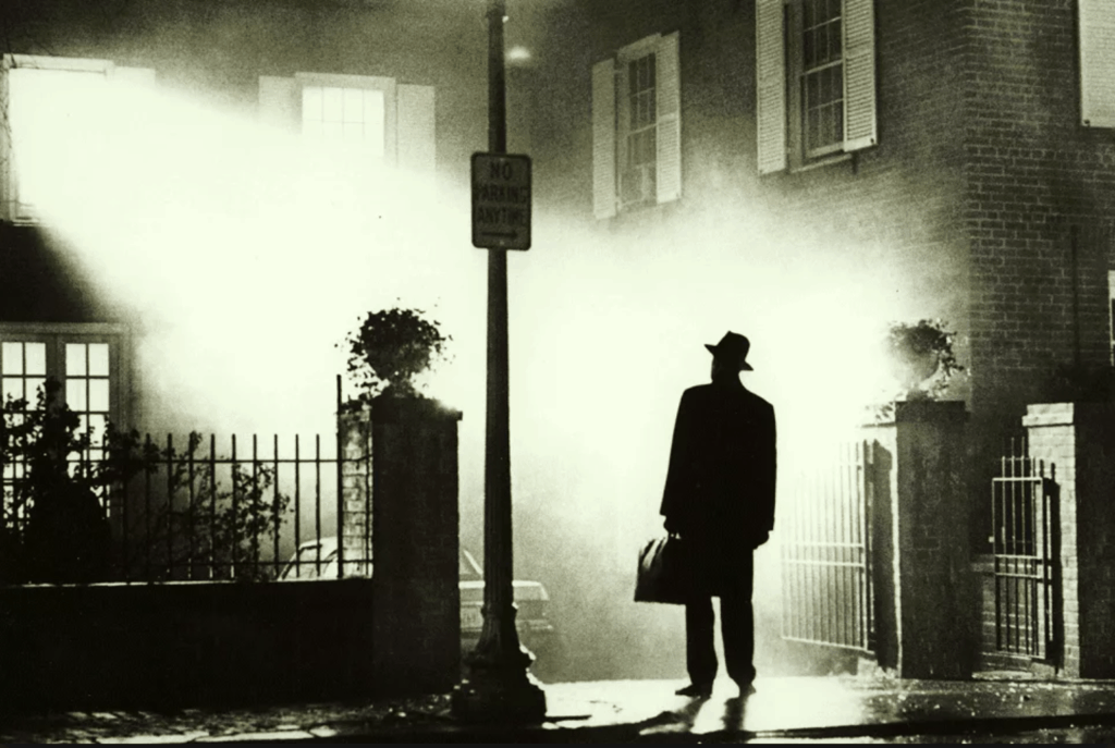 Priest stands in front of house in classic shot from The Exorcist